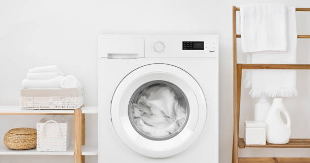 Washing machine with laundry and shelves on white wall background stock photo