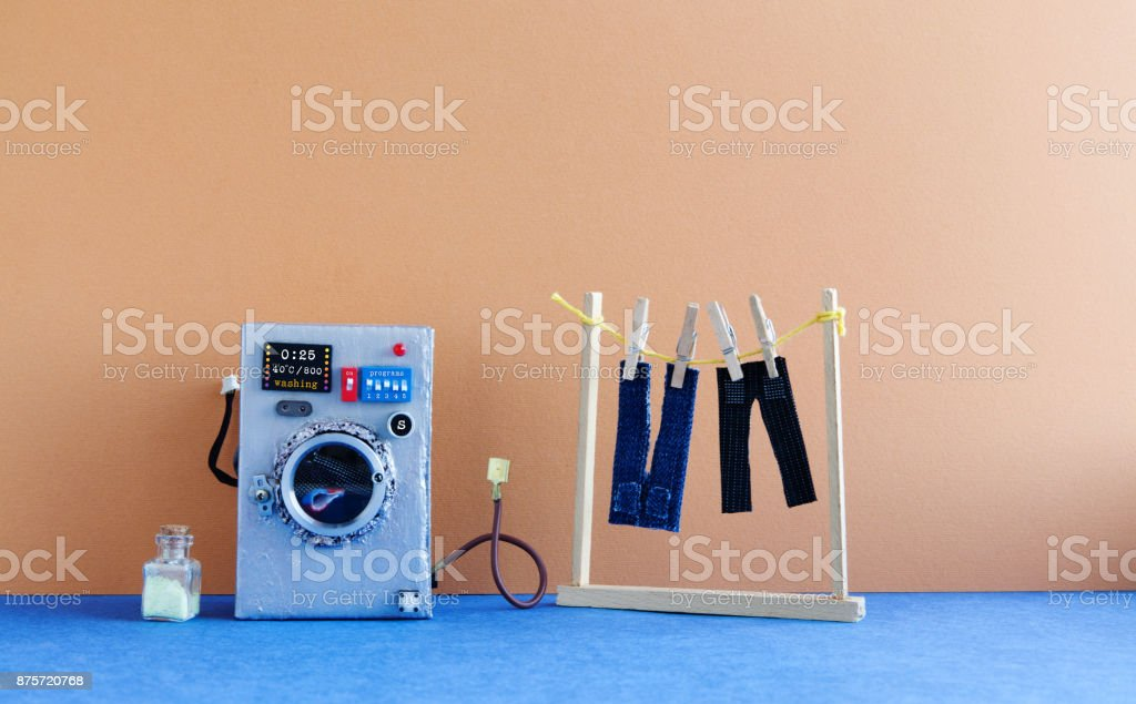 Washing machine with laundry, men's jeans pants dried on clothesline with clothespins. Brown wall interior, blue floor. Funny toys creative design stock photo