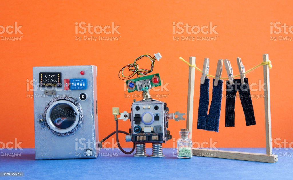 Washing machine with laundry, men's jeans pants dried on clothesline with clothespins. Robot handyman washhouse concept. Orange wall interior, blue floor. Funny toys creative design stock photo