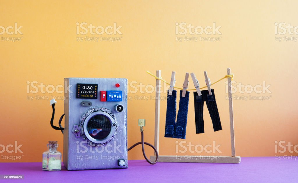 Washing machine with laundry, men's jeans pants dried on clothesline with clothespins. Yellow wall interior, violet floor. Funny toys creative design stock photo