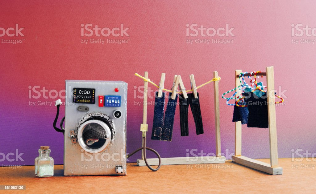 Washing machine with laundry room, men's jeans pants dried on clothesline with clothespins. pink biolet wall interior, brown floor. Funny toys creative design stock photo