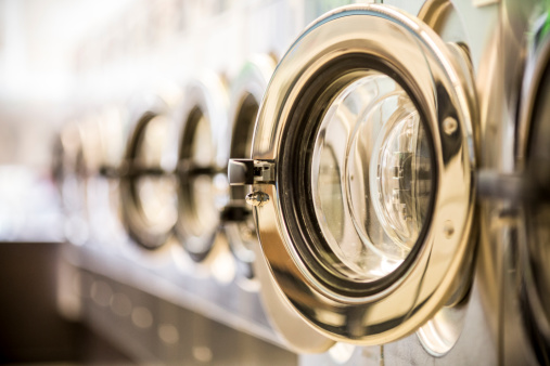 istock Washing machines - clothes washer's door in a public launderette 169982509