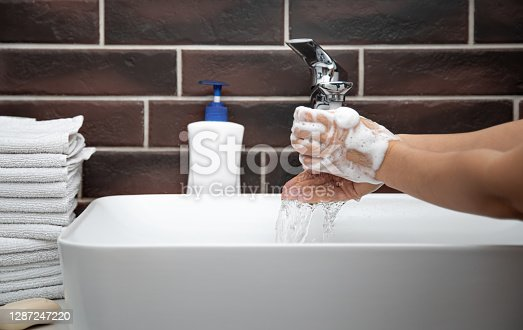 Washing hands with running water in the bathroom. The concept of personal hygiene and health.