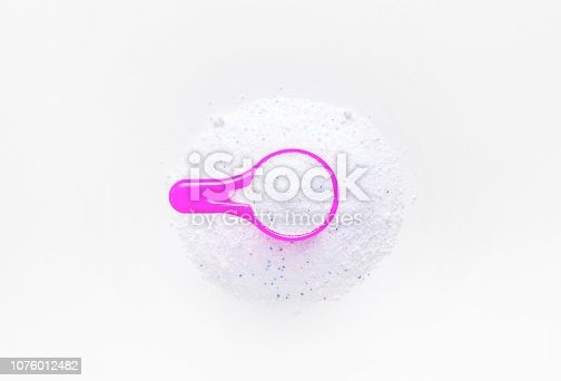 istock Washing powder in a measuring cup on a white table. 1076012482