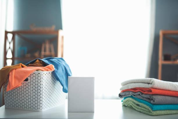 pulver-stehen waschen in der nähe von gefalteten wäsche - fleckenentferner stock-fotos und bilder