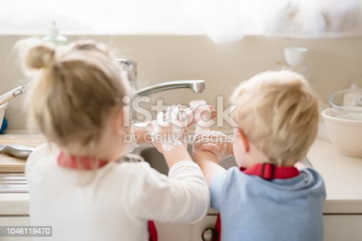 Siblings washing their hands with soap