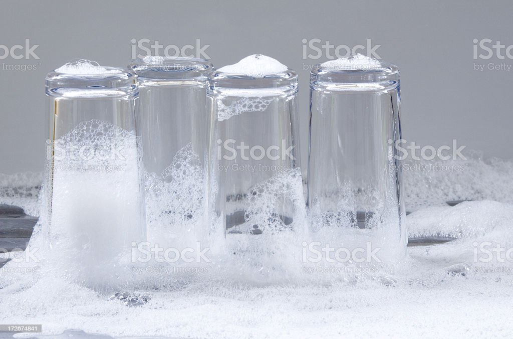 Washing up - four hi-ball glasses in bubbles royalty-free stock photo