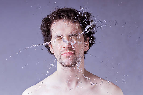washing up. handsome man with splashing water on his face. - drenched stock pictures, royalty-free photos & images
