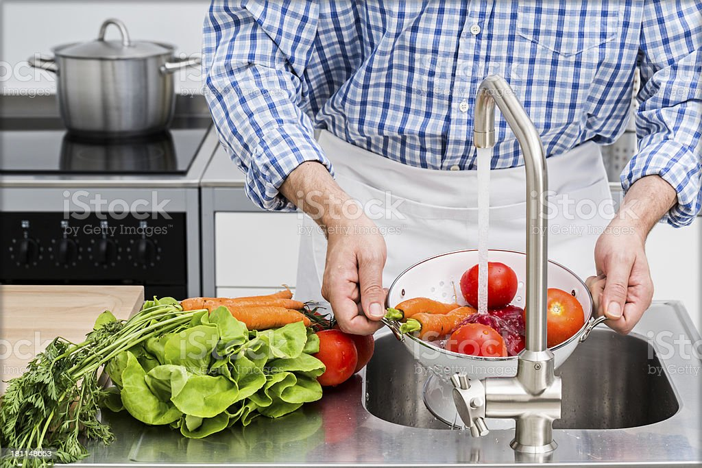 Washing vegetables in kitchen royalty-free stock photo