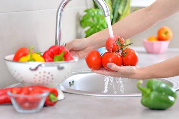 gemüse waschen. - grundnahrungsmittel stock-fotos und bilder