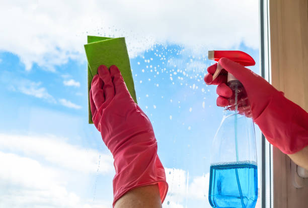 Washing windows. A cleaner in pink rubber gloves pokes a wiper onto the glass and wipes it with a green rag stock photo