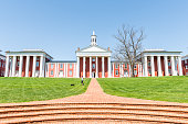 Washington and Lee University hall in Virginia exterior facade during sunny day with woman walking down, exterior brick architecture