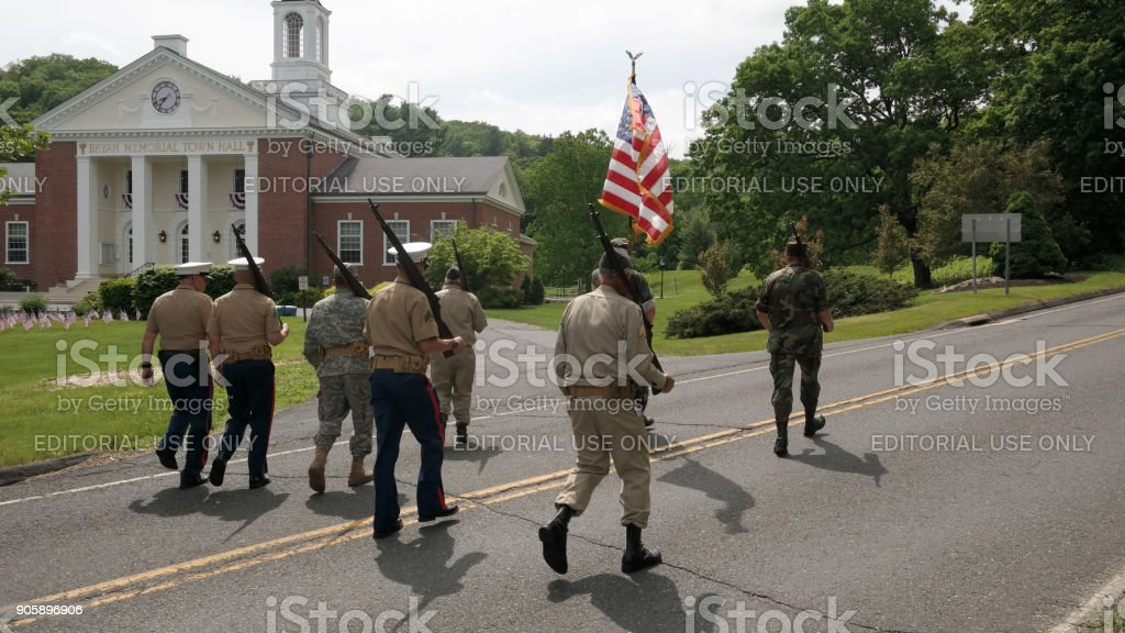 Washington Depot, CT, USA 05.30.2016 veterans day parade participants in uniforms carrying American flag with Bryan Memorial Town Hall in background stock photo