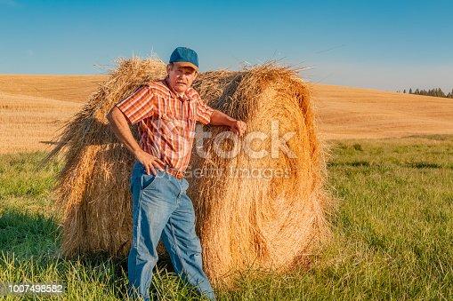 farmer with hayroll, farmer in wheat field, farmer with hand on hayroll