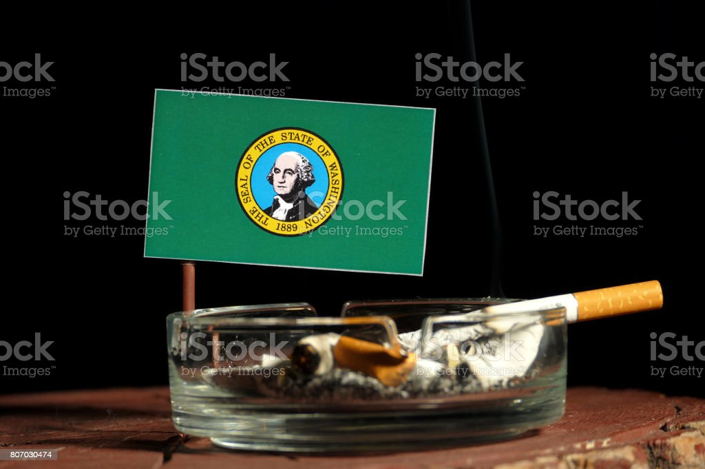 Washington flag with burning cigarette in ashtray isolated on black background stock photo