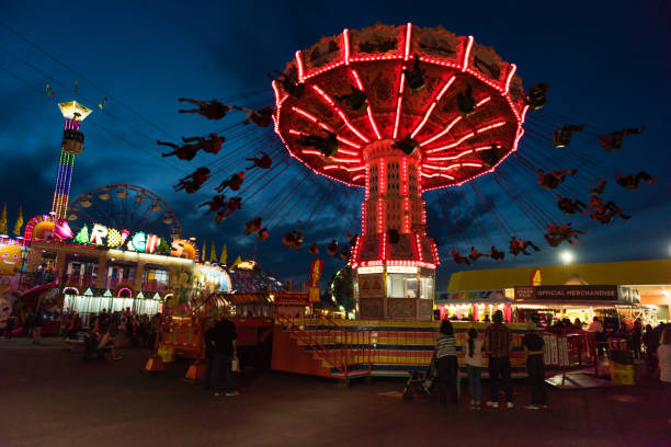 Washington State Fair Puyallup: People enjoying the illuminated rides at the Washington State Fair in Puyallup at twilight. The Fair is known by locals as the Puyallup fair and has been running since 1900. pierce county washington state stock pictures, royalty-free photos & images