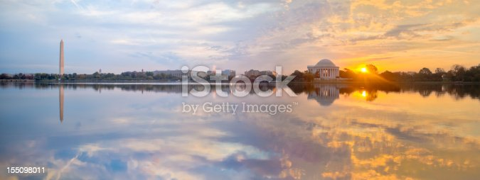 Panoramic image of the Tidal Basin at sunrise with the Washington Monument and the Jefferson Memorial.