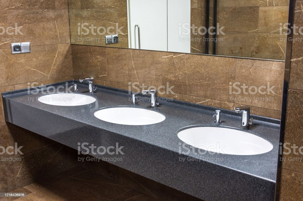Washstands With Integrated Liquid Soap Dispensers And A Mirror On The Wall In Public Toilet Brown Marble Stock Photo Download Image Now Istock