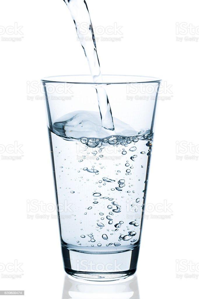 Wasser in Glas eingießen stock photo
