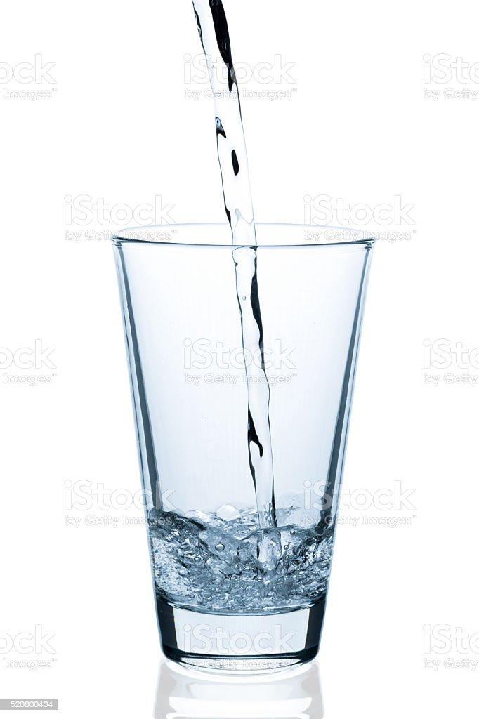 Wasser in leeres Glas eingießen stock photo