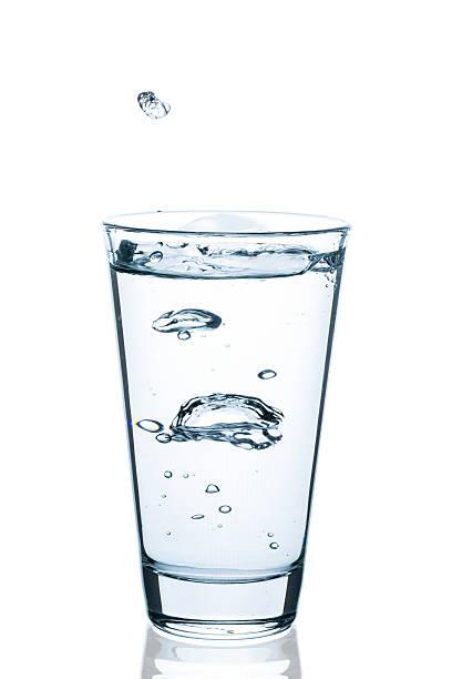 wasserglas mit spritzendem wasser und tropfen - wasser stock pictures, royalty-free photos & images