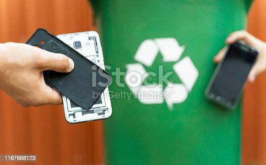 E waste , recycle concept , disassembled smartphone and recycle bin in background