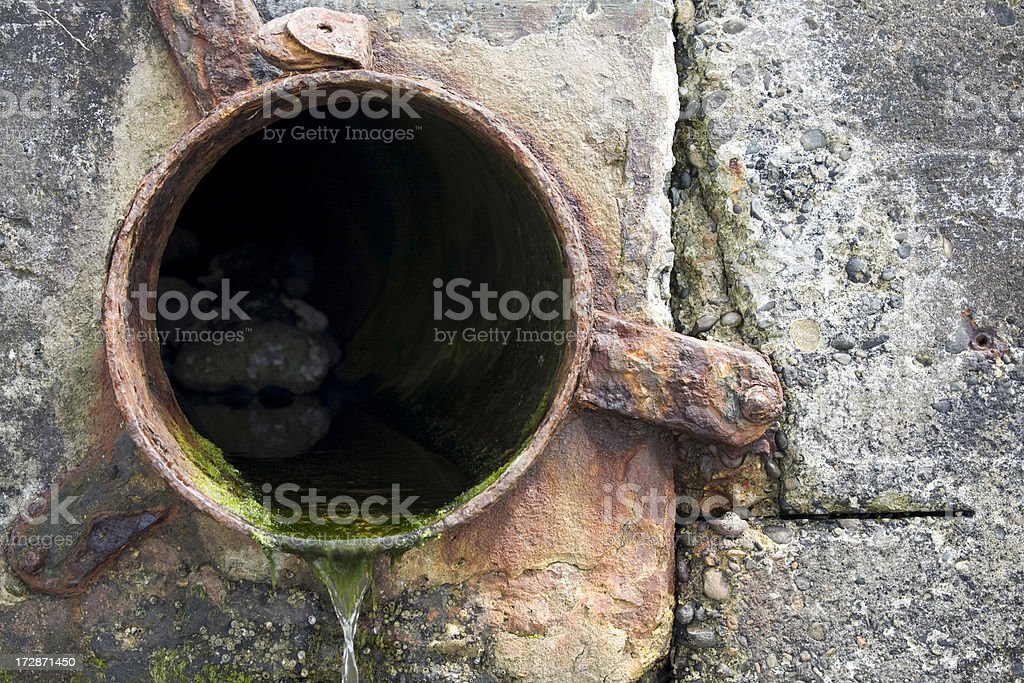 Waste drain pipe in concrete wall; environmental damage royalty-free stock photo