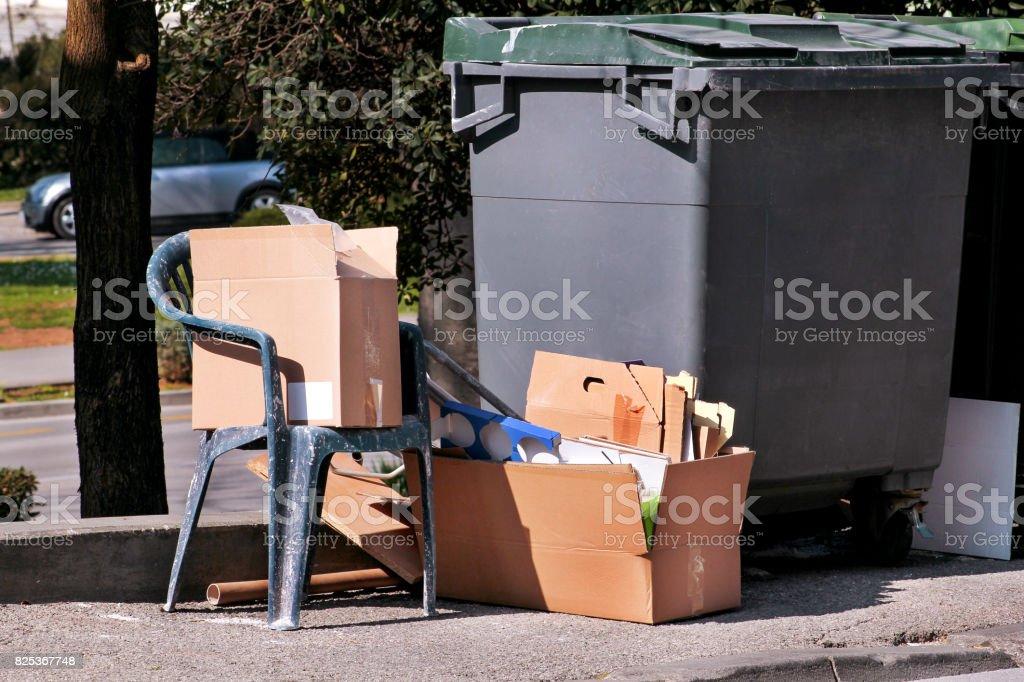 Esquerda ao lado de lixo de resíduos lixo na rua. Caixas de papelão e velha cadeira de plástico perto o contentor, contentores de lixo. Sujo, recusa escaninhos. Cena de rua. Indústria de reciclagem. Ecologia. Não de ecologia. - foto de acervo
