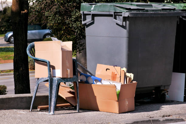 Waste left next to trash dumpster on the street. Cardboard boxes and old plastic chair near the container, trash dumpsters. Dirty refuse bins. Street scene. Recycling industry. Ecology. Not Ecology. stock photo