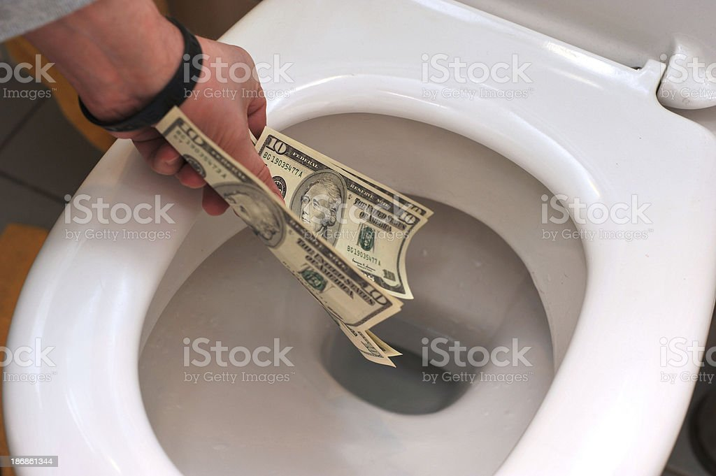 waste money dollars in toilet stock photo