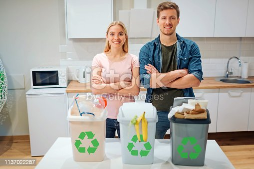 1137022221 istock photo Waste sorting at home. Protect the environment. Young happy family put waste in colorful garbage bins with green recycling icon in the kitchen 1137022287