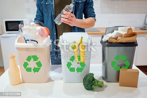 1137022295 istock photo Waste sorting at home. Recycling. Man putting plastic bottle in the garbage bin in the kitchen 1137022295