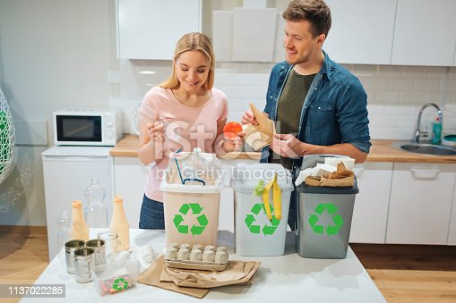 1137022221 istock photo Waste sorting at home. Smiling young couple putting plastic, paper, other waste in garbage bio bins in the kitchen 1137022285