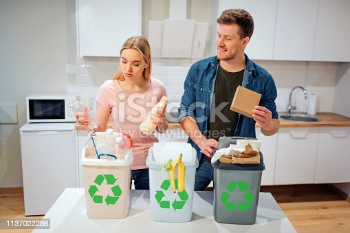 1137022221 istock photo Waste sorting at home. Smiling young family putting plastic, paper, other waste in garbage bio bins in the kitchen 1137022286