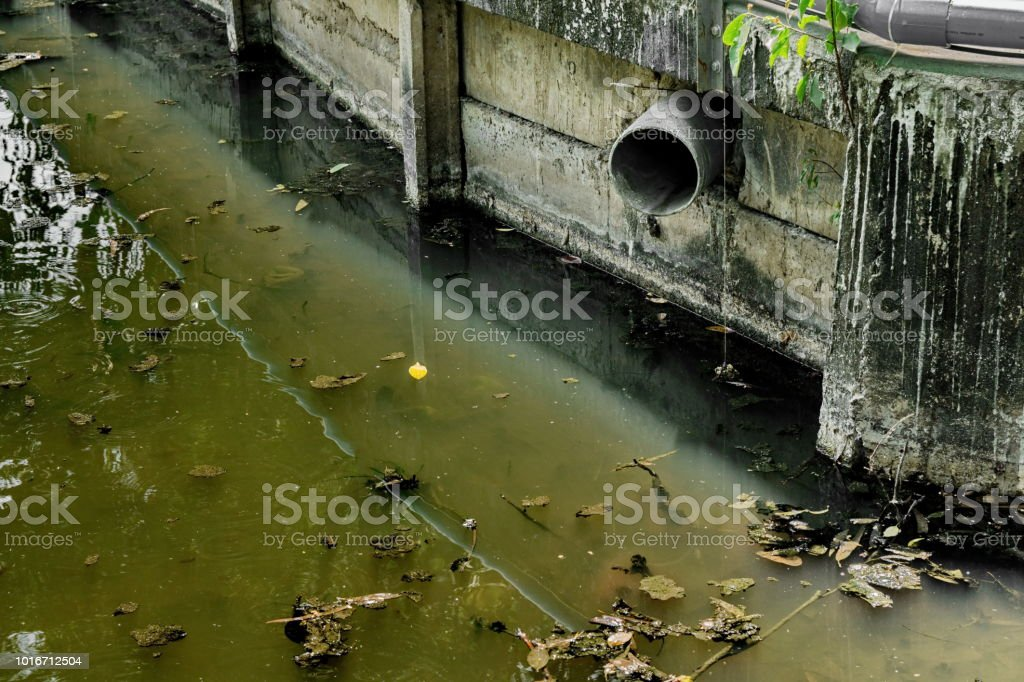 Waste water drain from industrial to the river, pollution problem стоковое фото