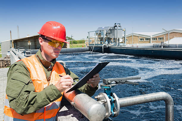 Waste water An engineer controlling the quality of water , aerated activated sludge tank at a waste water treatment plant sewage stock pictures, royalty-free photos & images