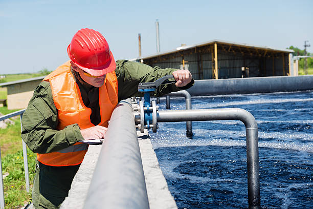 Waste water An engineer controlling the quality of water , aerated activated sludge tank at a waste water treatment plant .Copy space sewage treatment plant stock pictures, royalty-free photos & images