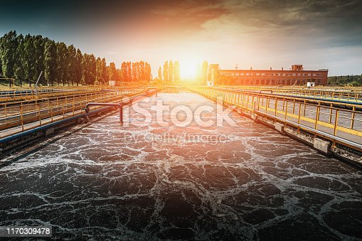 Wastewater treatment plant at sunset. Tanks for aeration and cleaning of sewage mass, toned