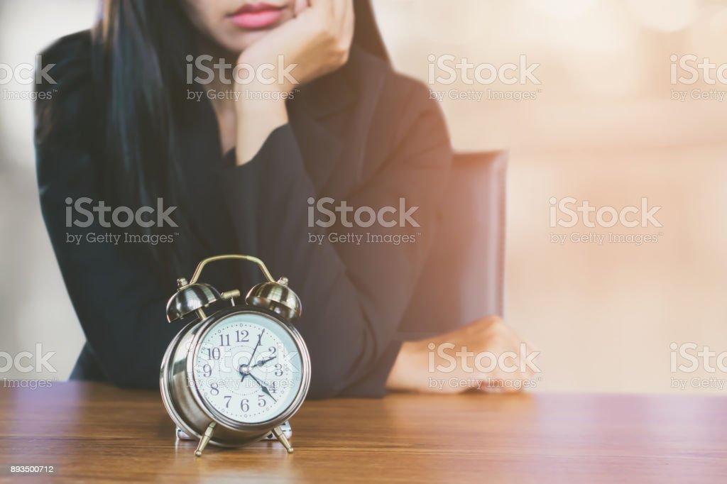 Wastiwasting Konzept mit asiatischen Geschäftsfrau müde und gelangweilt wartet auf jemanden mit Wecker auf Schreibtisch ng Konzept mit Business-Frau warten Someonecome späten Wecker auf Schreibtisch mit betrachten unglücklich Gesicht – Foto