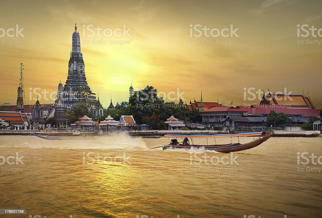 Wat Arun across Chao Phraya River during sunset with boat stock photo