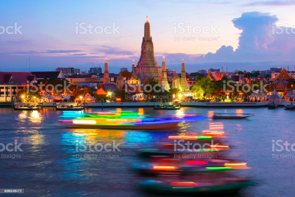 Wat Arun at dusk with boats are running through. stock photo