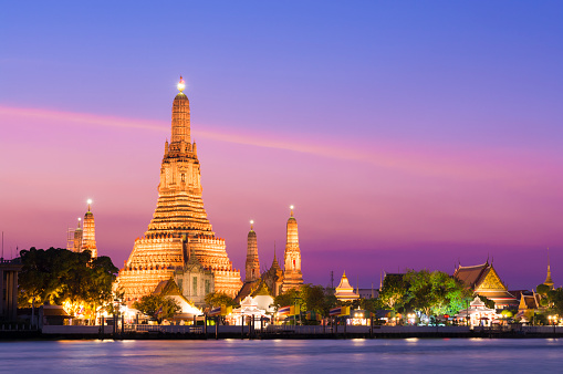 The illuminated temple of Wat Arun on the Chao Phraya river at sunset in Bangkok, Thailand