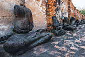 Headless Buddha Statues in a row near a brick wall in Buddhist Temple Wat Maha That, Ayutthaya historical park, Thailand.
