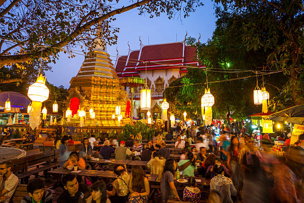 "Wat Phra Singh on market night in Chiang Mai ""Chiang Mai, Thailand - December 11, 2011: Many people sit at tables and eat at the market outside Wat Phra Singh on market night where many food stalls can be found within the temple courtyard."" chiang mai province stock pictures, royalty-free photos & images"