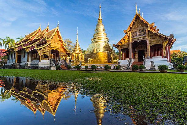 Wat Phra Singh temple and reflection in water. Chiang Mai Wat Phra Singh temple, blue sky and reflection in water. Chiang Mai, Thailand. chiang mai province stock pictures, royalty-free photos & images