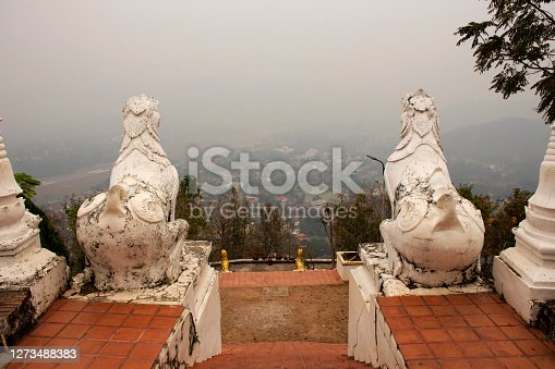 White singha statue guardian at Wat Phra That Doi Kong Mu Temple with landscape and cityscape of Maehongson hill valley city in Mae Hong Son, Thailand for Thai people and foreign traveler travel visit
