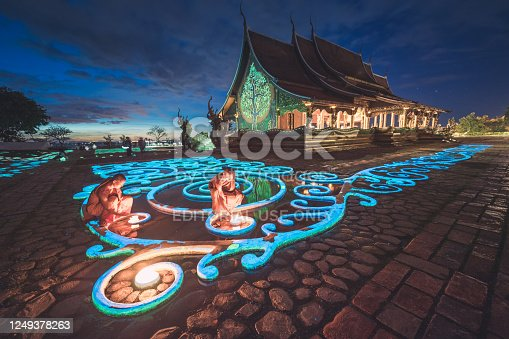 Ubon Ratchathani , Thailand - November 23, 2015 ; Group of monk light candle and praying in Sirindhorn Wararam Phu Prao is public Temple (Wat Phu Prao) at evening a glow of the sculpture of the Kalpapruek, which is attached to the wall behind the church.It will appear green glow in the night
