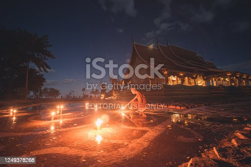 Ubon Ratchathani , Thailand - November 25, 2015 ; Group of monk light candle and praying in Sirindhorn Wararam Phu Prao is public Temple (Wat Phu Prao) at evening a glow of the sculpture of the Kalpapruek, which is attached to the wall behind the church.It will appear green glow in the night