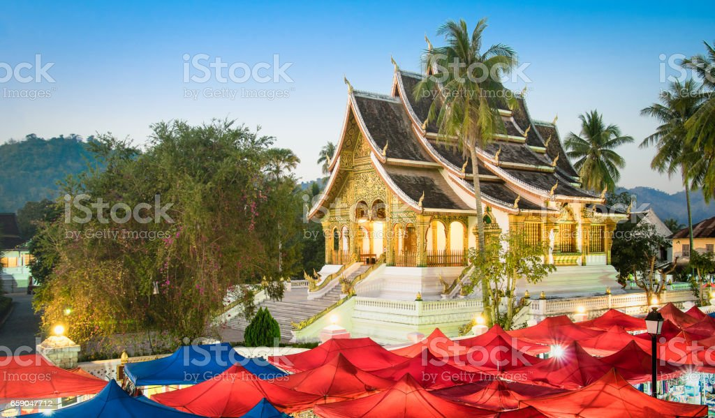 Wat Xieng Thong temple and night market at blue hour in Luang Prabang - Laos PDR world famous tourism destination - Travel concept with antique landmark in south east Asia exclusive city destinations stock photo