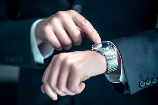 Watch around the wrist of a stylish business man. Busy businessman looking at the time. Stress or hurry at work. Person wearing suit and pointing at his wristwatch with finger. stock photo